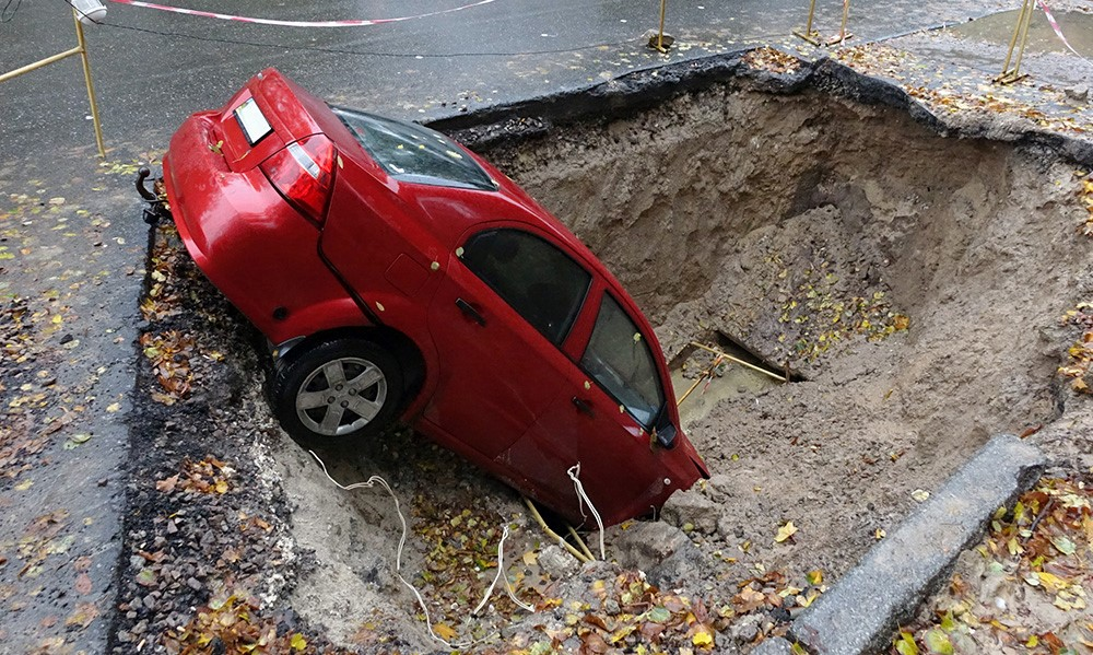 car in a large hole - fake news