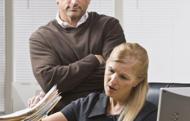micromanaging: businessman looking over employee's shoulder
